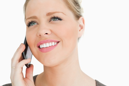 Woman calling with a cellphone against white background photo