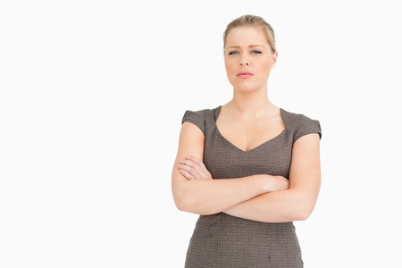 solicitous: Uneasy woman standing with her arms crossed against white background Stock Photo