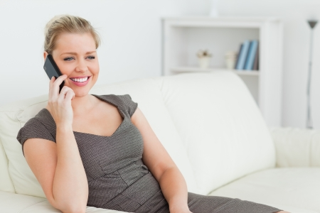 Woman calling while she is sitting on a sofa in a lounge photo