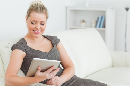 Woman looking at an ebook sitting on a sofa photo