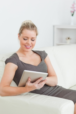 Woman touching screen of ebook sitting on a sofa photo