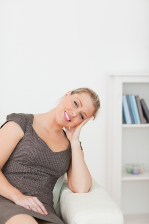 armrest: Woman sitting on a sofa with an arm on armrest in a lounge