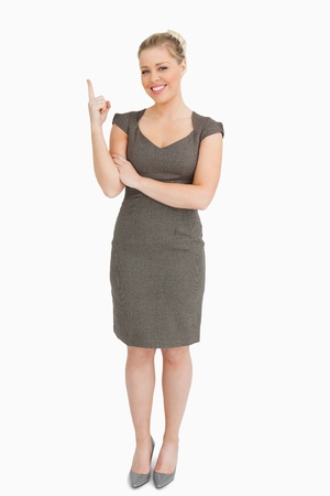 Woman smiling showing something with her finger against white background