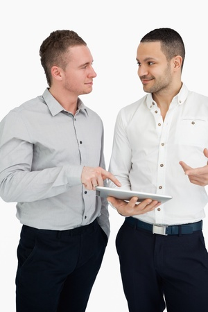 Two men together while holding a tablet computer against a white background photo