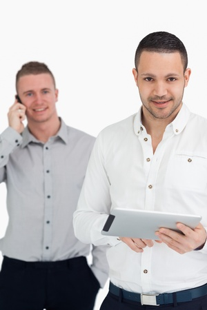 Two smiling men using phone and tablet computer against a white background photo
