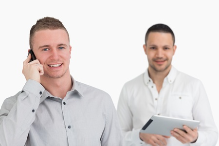 Two men with phone and tablet computer against a white background photo