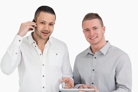 Smiling men holding a phone and a tablet computer against a white background Stock Photo - 16203165