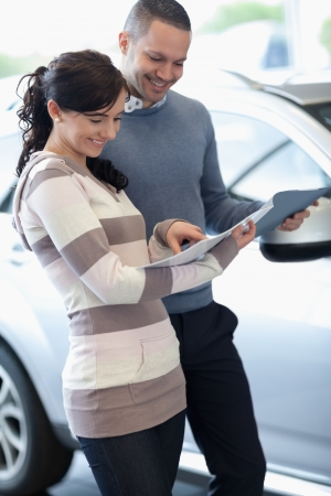 Couple holding documents in a carshop photo