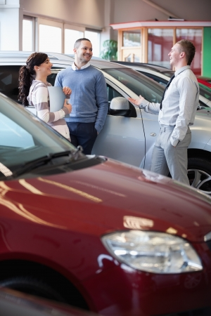 Smiling salesman chatting with customers in a carshop photo