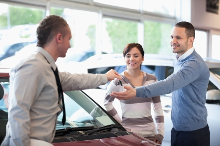 Smiling couple receiving keys from a car dealer in a car shop photo