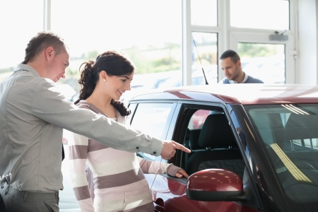 Car dealer pointing the interior of a car with a woman in a car shop photo