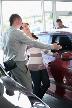 Woman talking with a salesman in a car shop photo