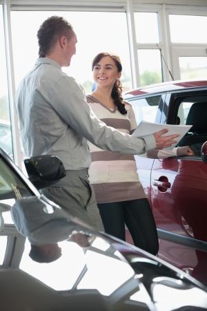Salesman showing documents ta a woman in a car shop photo