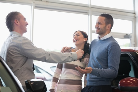 Laughing couple receiving keys from a salesman in a car shop photo