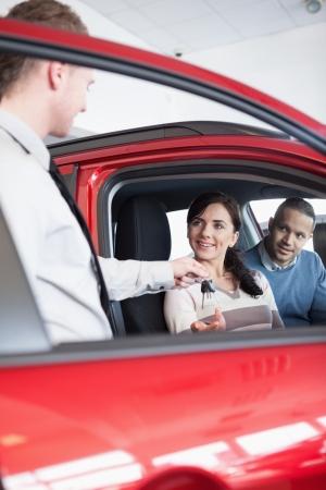 together with long tie: Sonriendo cliente recibe las llaves del coche a un vendedor