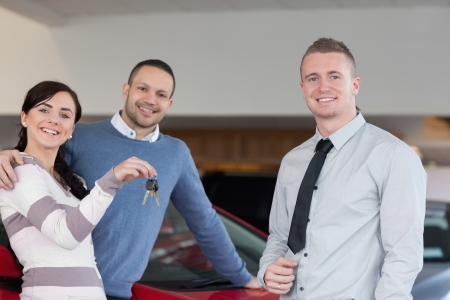 Salesman giving keys to an embracing couple in a car shop photo