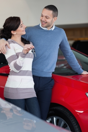 Couple standing next to a car while holding keys photo