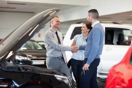 together with long tie: El hombre estrechando la mano de un concesionario de coches en frente de un coche en una tienda de coches