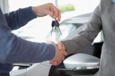 handing: People shaking each other hands while holding keys Stock Photo