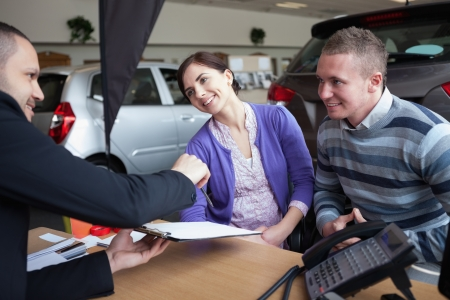 Couple chatting with a car salesman in a car shop photo