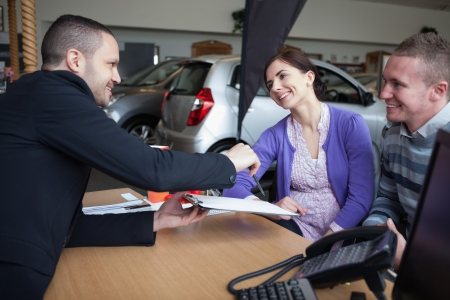 Salesman talking to a couple in a car shop photo