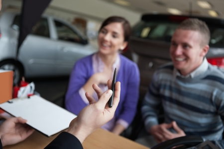 Couple listening to a car dealer in a car shop photo