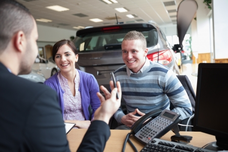 Couple smiling while talking with a salesman in a car shop photo