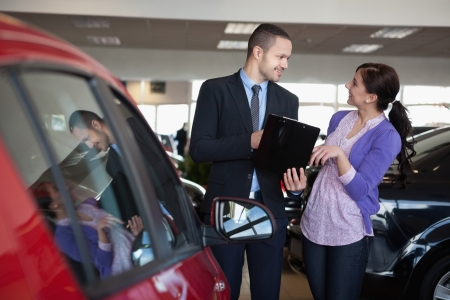 Salesman talking to a smiling woman next to a car in a car shop photo
