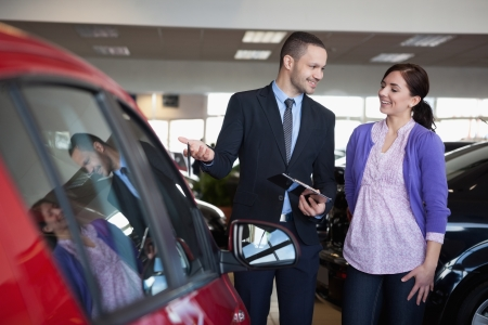 Salesman showing a car to a woman in a car shop Stock Photo - 16208609