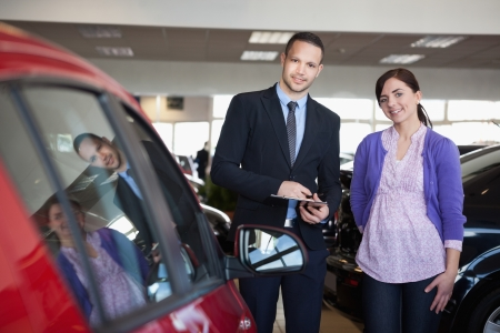 Woman and a salesman standing side by side in a car shop Stock Photo - 16208532