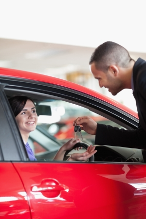 Smiling woman receiving car keys while sitting on a car Stock Photo - 16204977