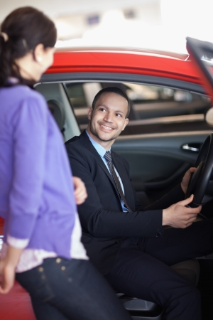 Man sitting in a car while talking to a woman in a car shop Stock Photo - 16204954
