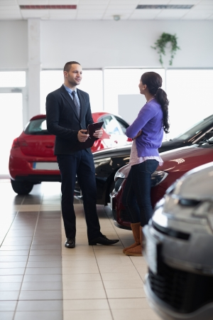 Salesman and a woman talking next to a car in a car shop photo