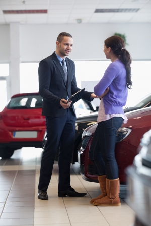 Salesman talking to a customer in a car shop photo
