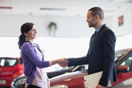 Salesman and a woman shaking hands in a car shop Stock Photo - 16205205