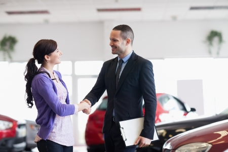 Smiling salesman shaking the hand of a woman in a car shop photo