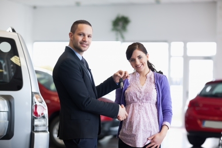 Salesman shaking hand and giving keys to a woman in a car shop photo