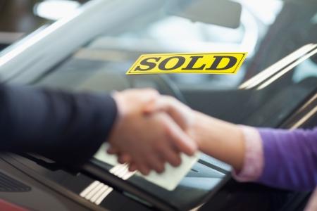vendiendo: Las personas d�ndose la mano delante de un coche vendido Foto de archivo
