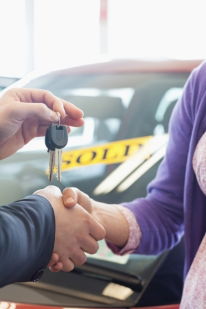 car retailer: Woman shaking the hand of a man in a car dealership Stock Photo