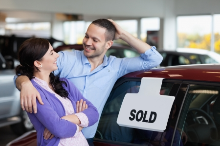 Smiling couple hugging next to a car in a car dealership photo