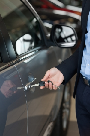Man opening a car with a key in a car dealership photo