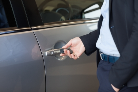 Man opening a car door with a key in a car dealership photo