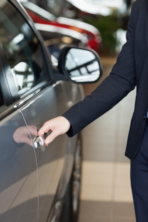 Man holding a car door handles in a car dealership photo