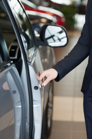 Man holding an half open door in a car dealership photo