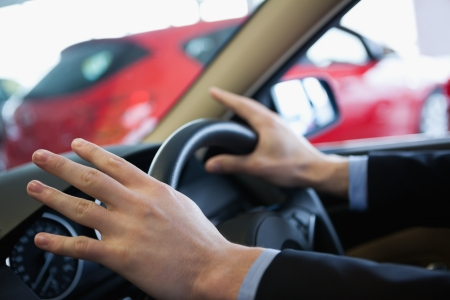 Man holding a steering wheel in a car dealership Stock Photo - 16207570