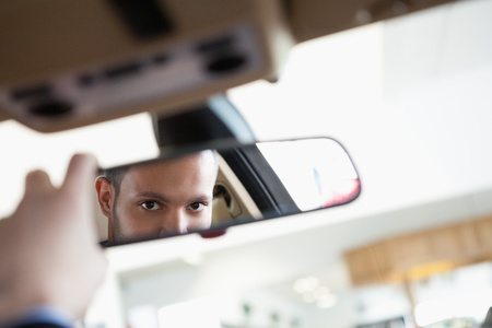 Man looking in an interior car mirror while sitting in a car Stock Photo - 16207754