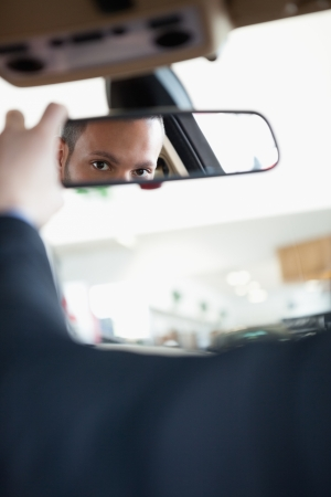 Man adjusting a rear view mirror while sitting in a car photo