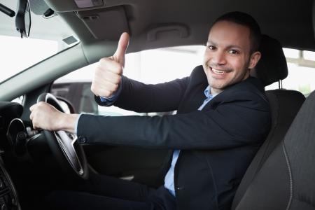 hombre conduciendo: El hombre que conduce un coche mientras sonre�a Foto de archivo
