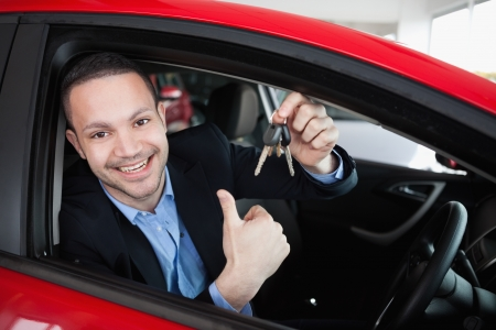 Happy man holding car keys while sitting in a car photo