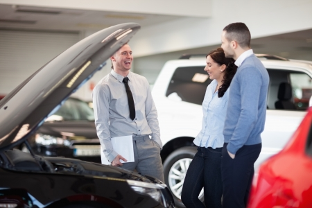 Salesman smiling as he talks to a couple in a car dealership photo